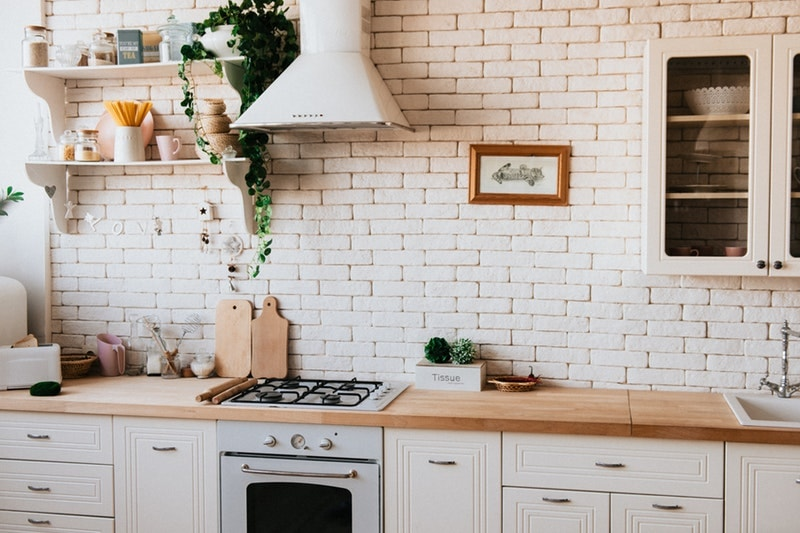 Kitchen cabinets surrounding stove against a brick backsplash
