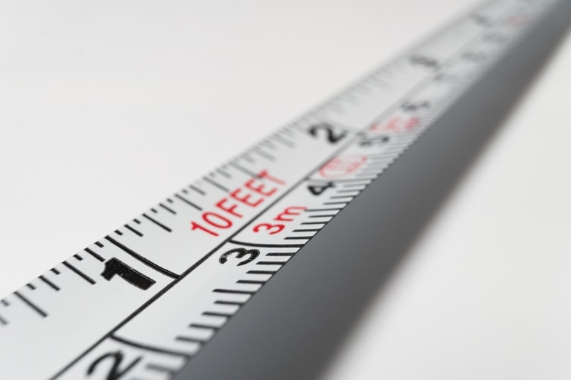 A close-up of white measuring tape along a white surface