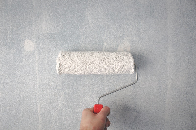 Person holding a paint roller on a wall