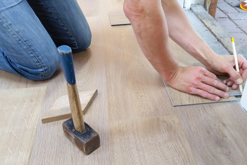 A person marking the trim along the floor