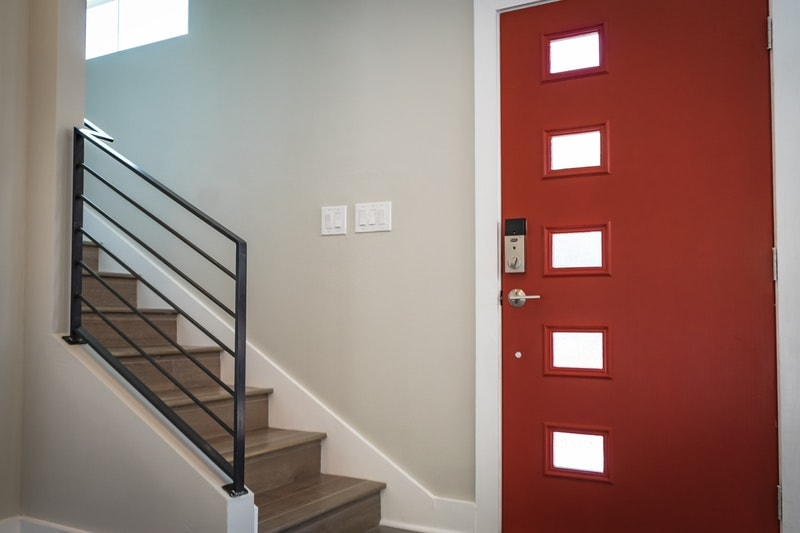 A red door with white trim next to a set of stairs