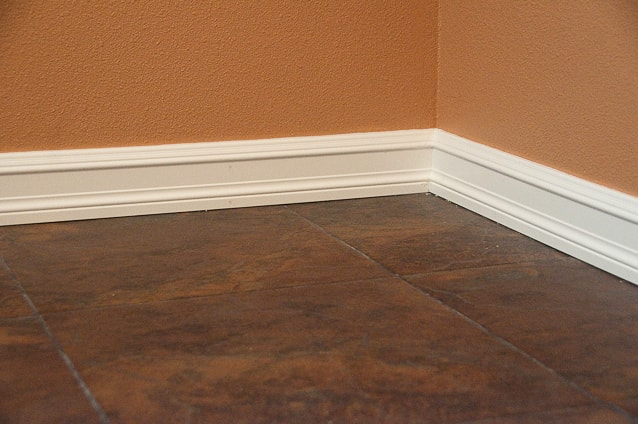 A close-up of white baseboard running along an orange wall and brown tiled flooring