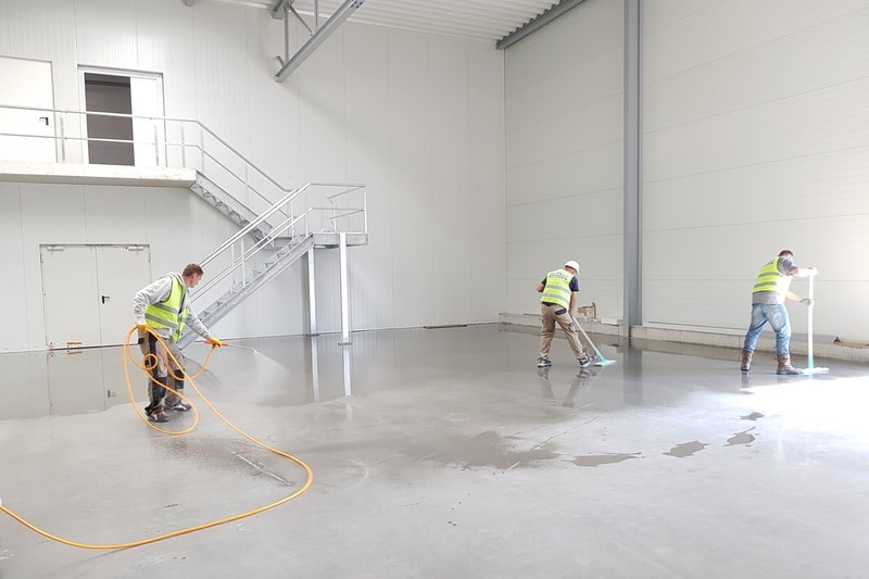 Concrete flooring being sprayed clean by professionals