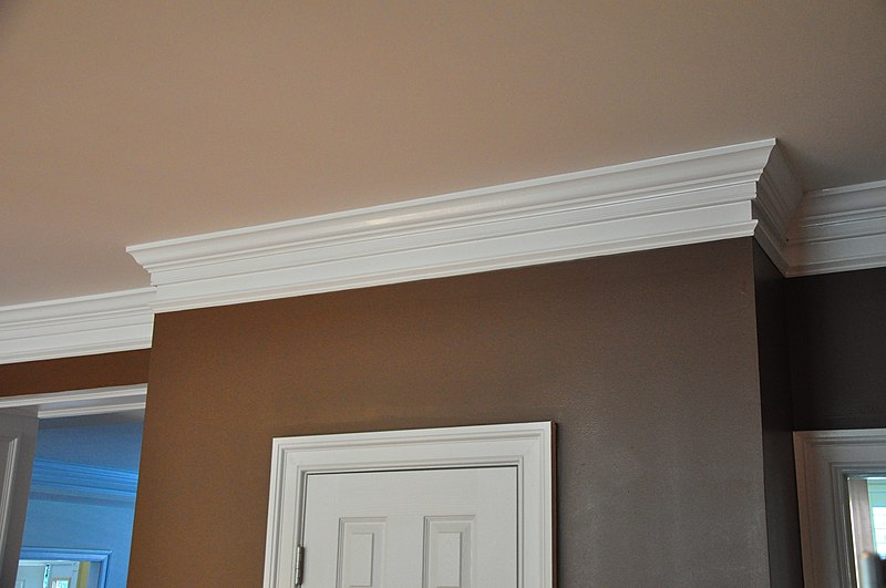 White, wooden crown molding running along the ceiling