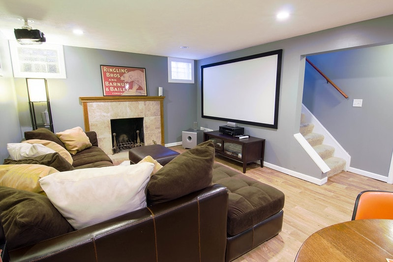 A painted basement living area with gray walls and a white ceiling