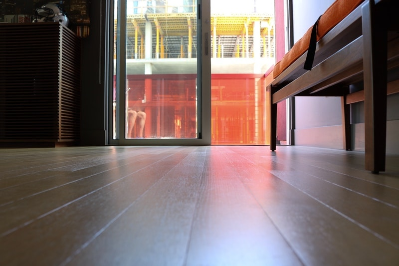 A closeup of a painted floor in the sunlight with a sliding door leading outside straight ahead