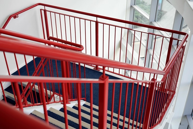 A multi-level staircase with red-painted metal railings