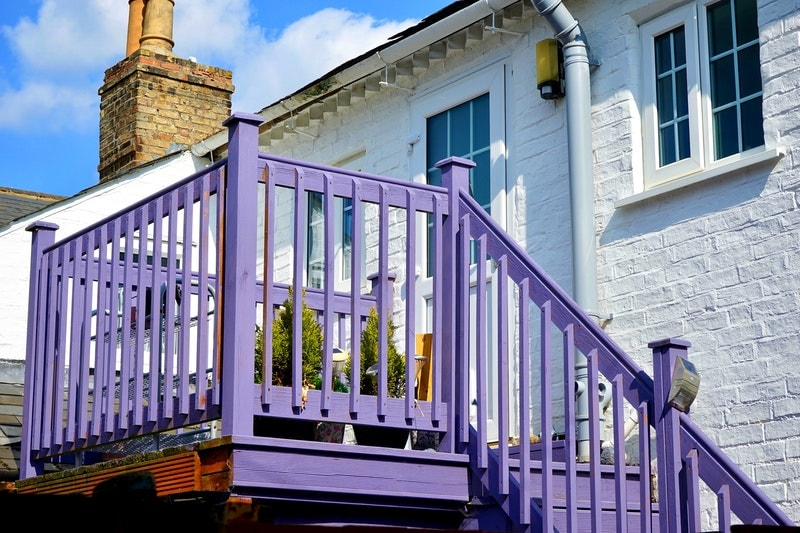 A white house with a deck and stairs that have been painted purple