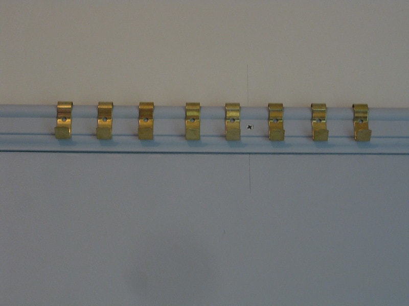 A close-up of a picture rail with gold hooks along it