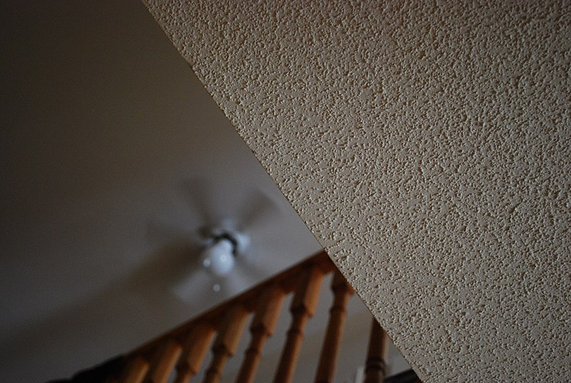 A close-up of a popcorn ceiling with a light shining in a dim room