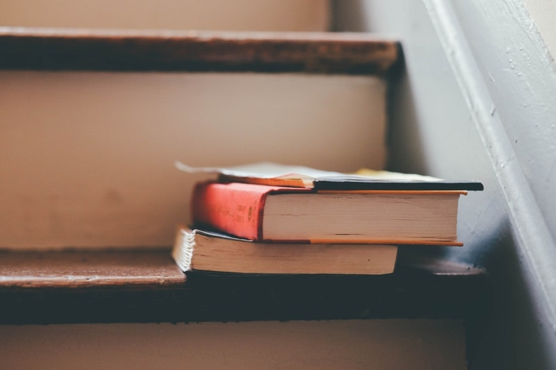 A close-up of two books on a wooden staircase with beige risers
