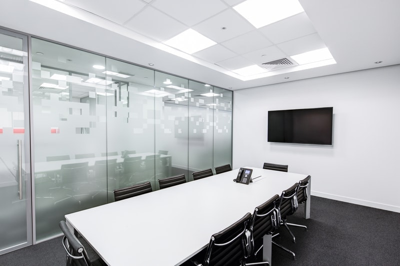 A meeting room with a drop tile ceiling