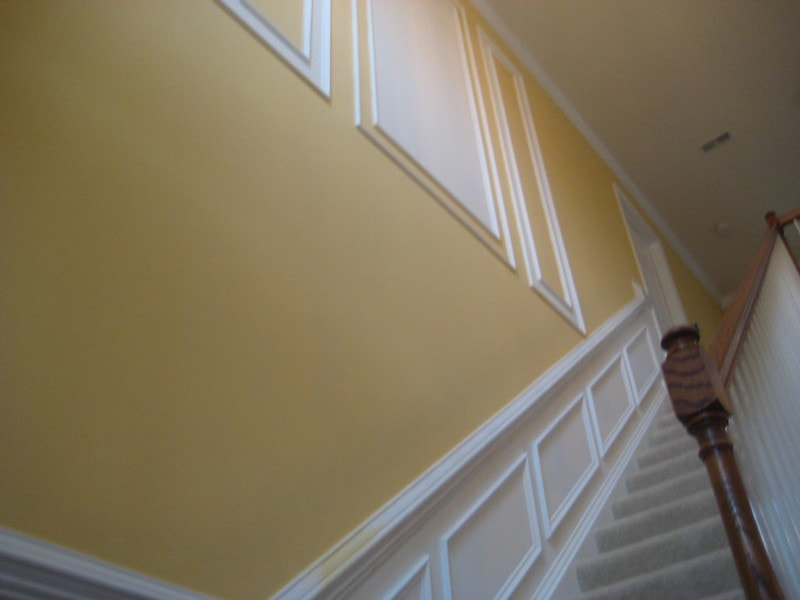 An upward shot showcasing wall frame molding along the stairs and on a yellow wall