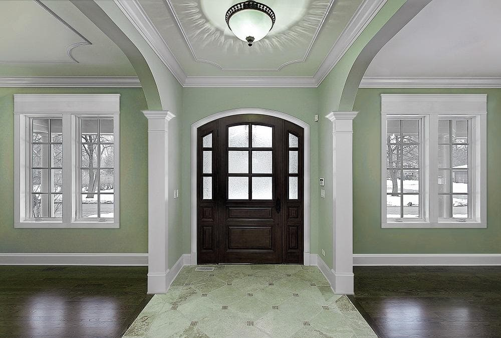 A front foyer with crown molding around the windows and doors