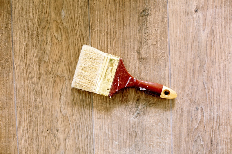 A flat-edged paint brush on a wooden floor
