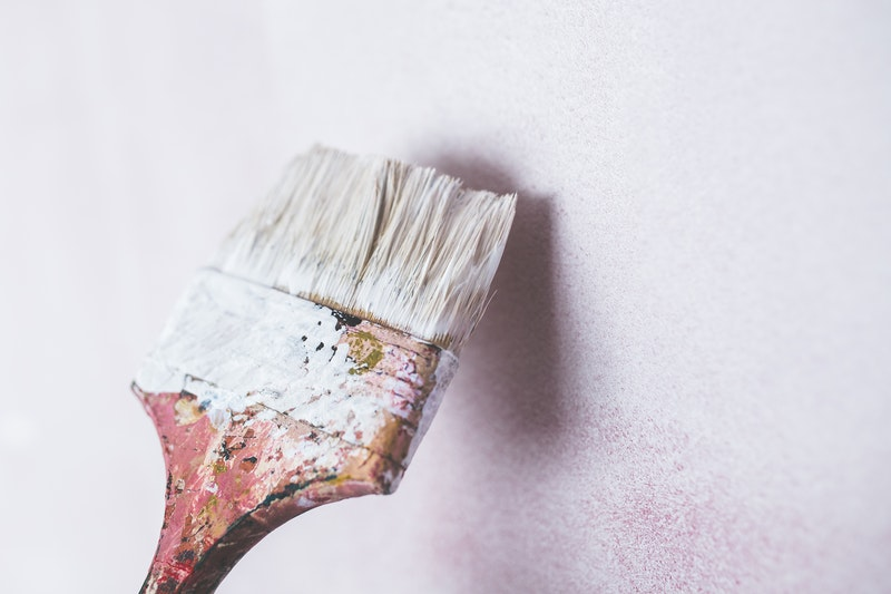 A flat paint brush applying white paint to a white wall