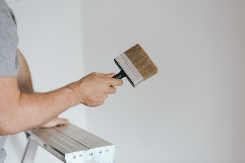 A painter holding a brush, preparing to paint a wall