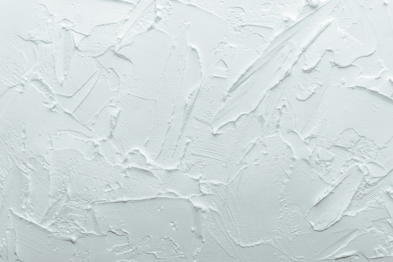 A closeup of a bright white textured wall