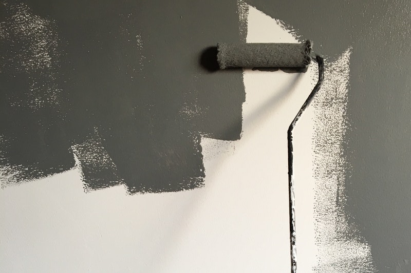 A roller painting dark grey paint on a white wall