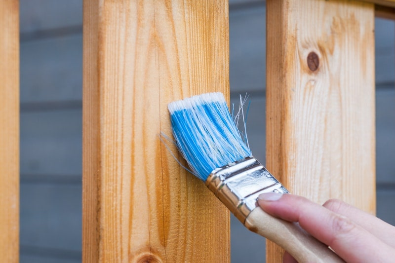 A close-up of a paint brush being used to apply stain to a wooden fence