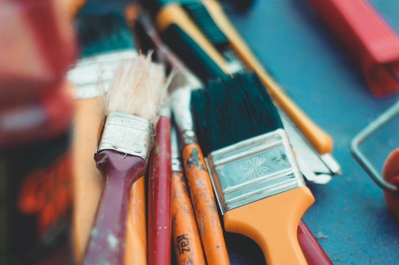 A closeup of a small pile of different paint brushes