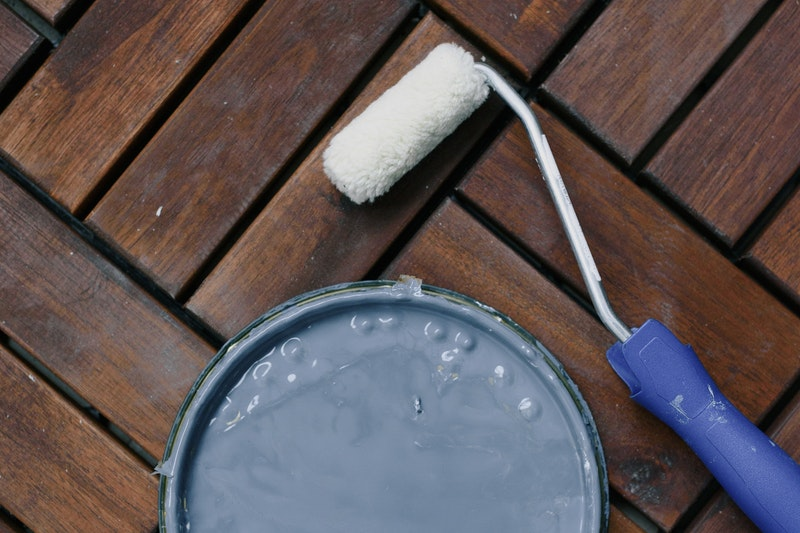 A roller on a wooden floor next to a paint can lid