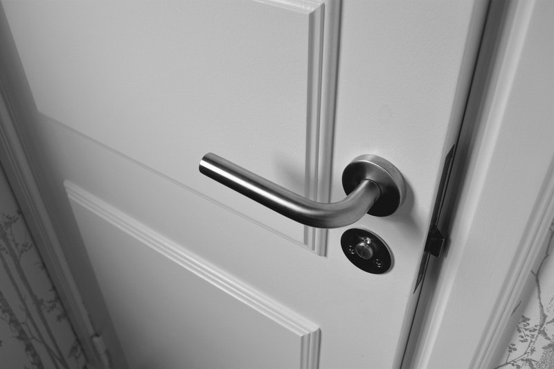 A close-up of a white painted door with matching trim