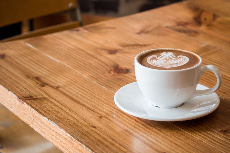 A close-up of a latte sitting on a polyurethane-coated wooden table\