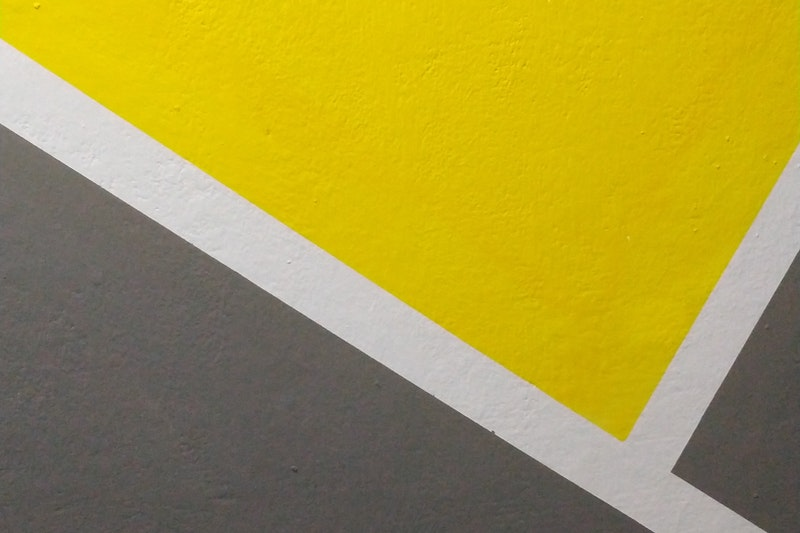 A closeup of a grey, yellow, and white design on a concrete wall