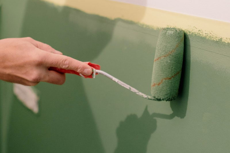 A closeup of a paint roller being used to apply green paint to part of a wall