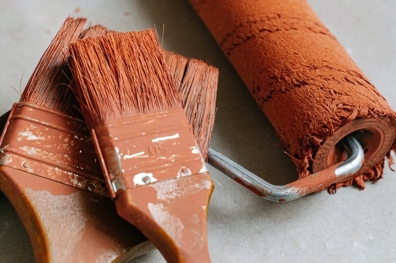 A closeup of paint brushes and a roller covered in orange paint