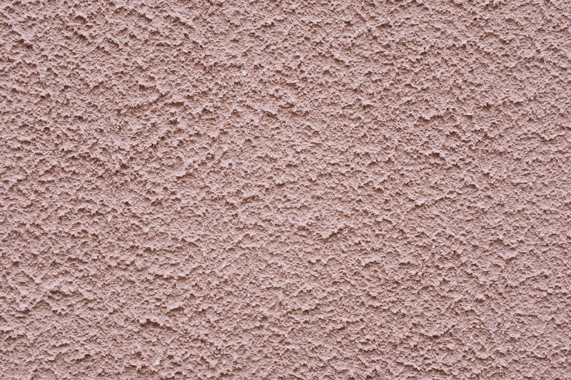 A closeup of the painted stucco texture on a wall