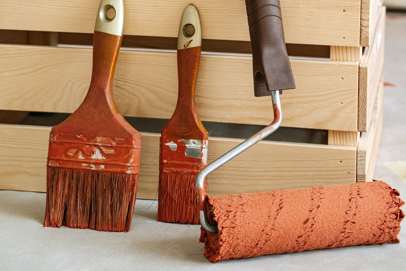 A closeup of two brushes and a roller covered in orange paint