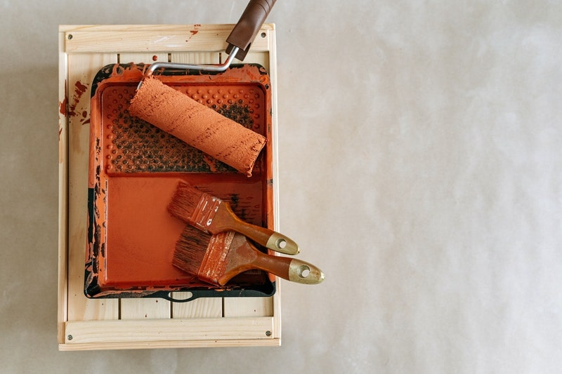 A photo of a roller and brushes inside a paint tray filled with orange paint