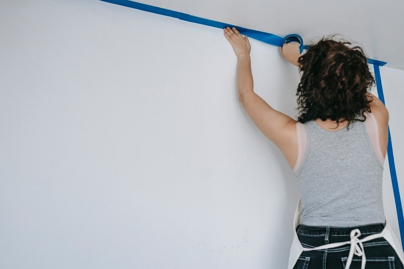 A woman applying blue painter's tape along the edge of a ceiling