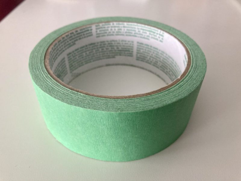 A closeup of a roll of green painter's tape