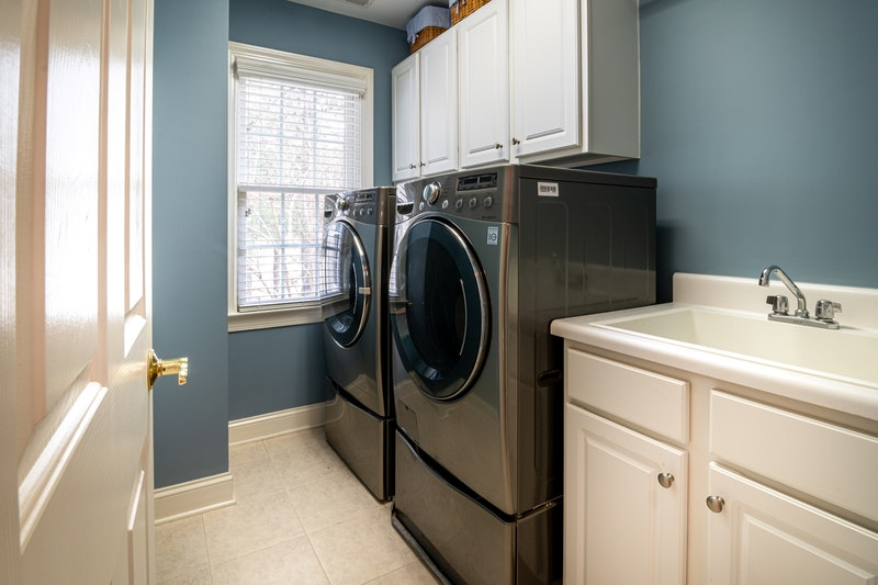 A laundry room with nicely painted cabinets