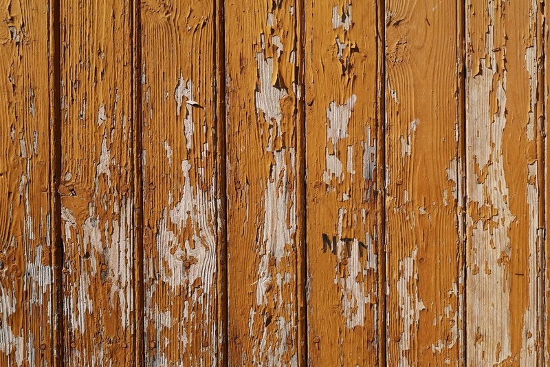 A closeup of aging wood paneling covered in chipped paint