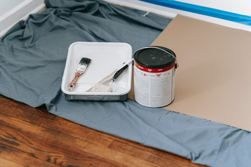 A closeup of a paint tray with a roller and brush next to a can