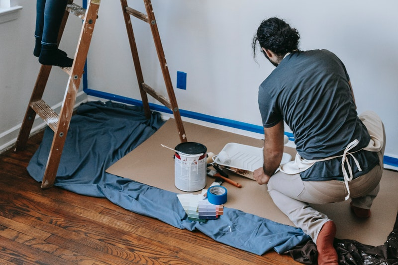 A man working on a drop cloth as another person stands on a ladder