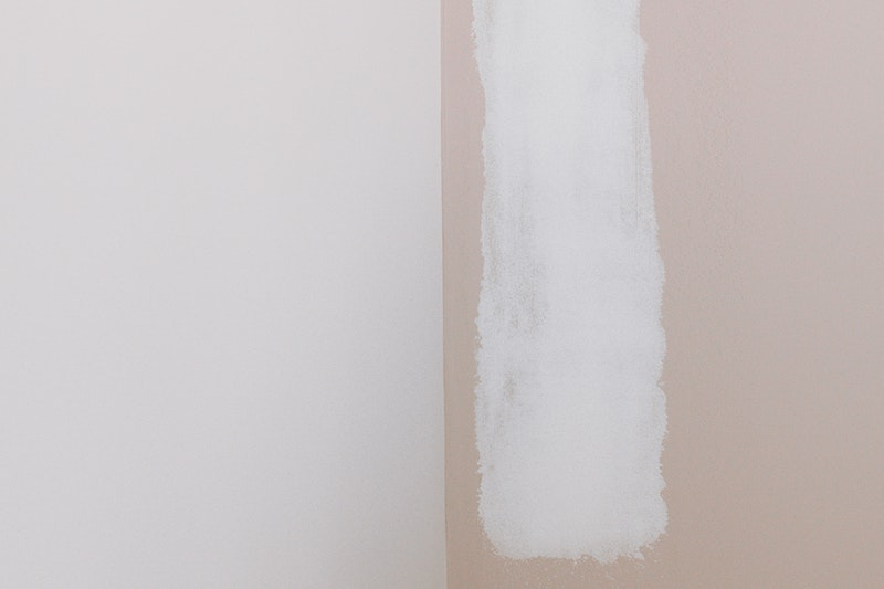 A closeup of primer partially applied to a wall