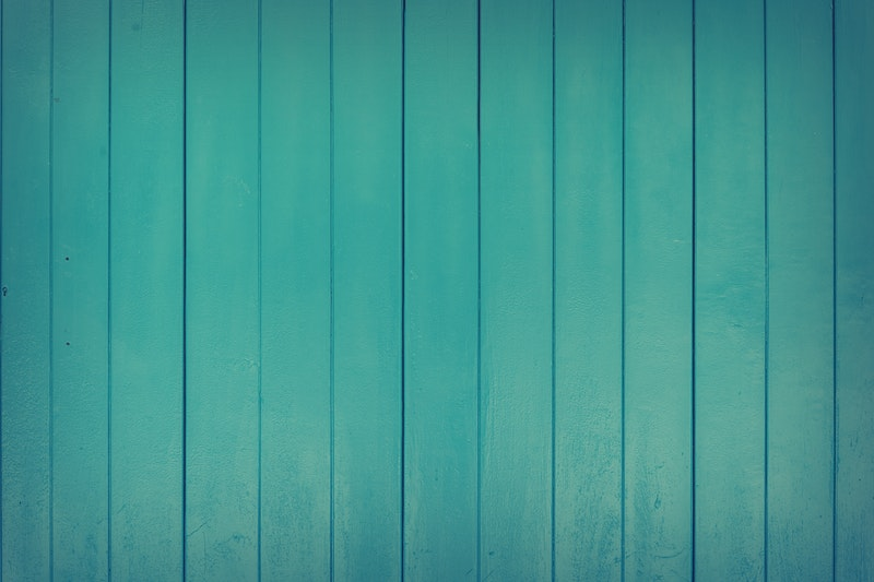 A closeup of wood paneling that has been painted teal