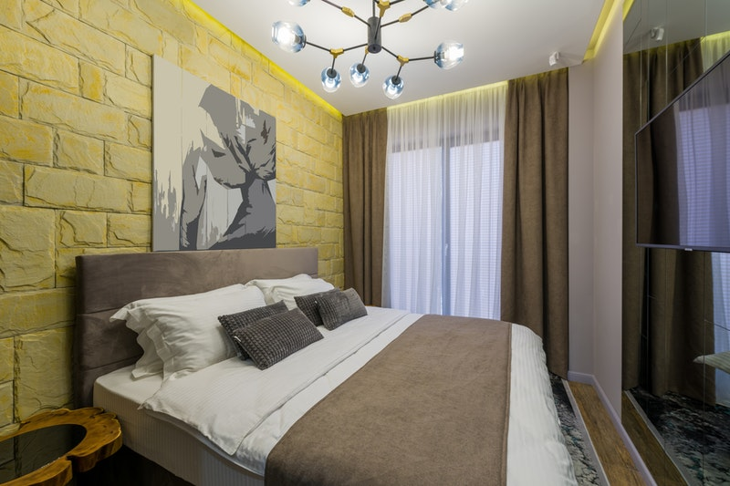 A bedroom with yellow painted brick