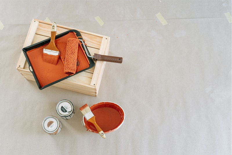 Paint brushes in a tray containing orange paint